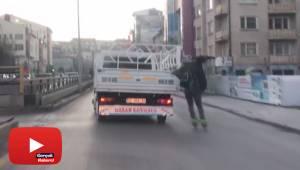 Patenli genç kamyonun arkasına tutunup tehlikeye aldırış etmeden dans etti